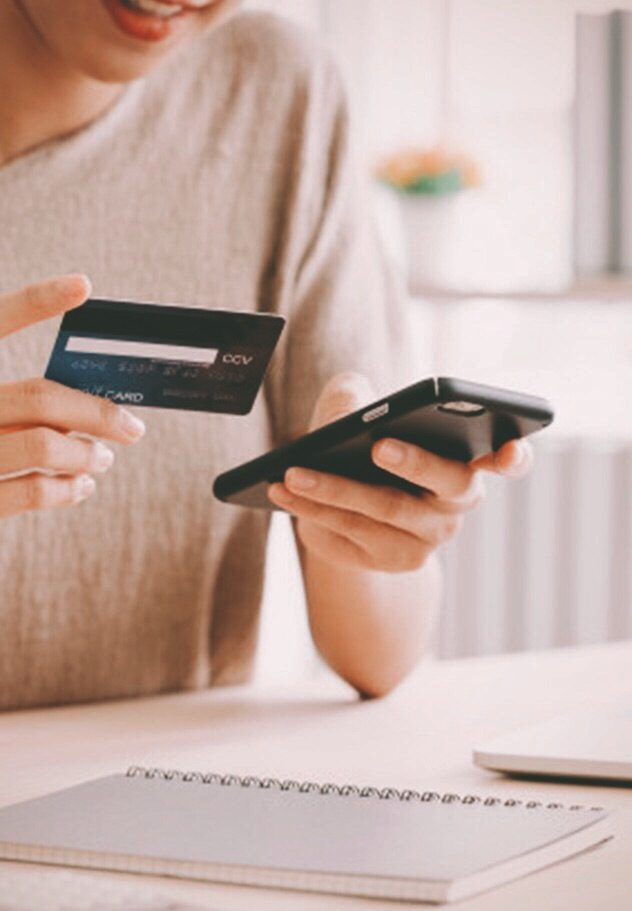 Woman holding mobile phone and debit card